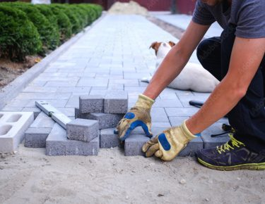 Garden brick pathway paving by professional paver worker