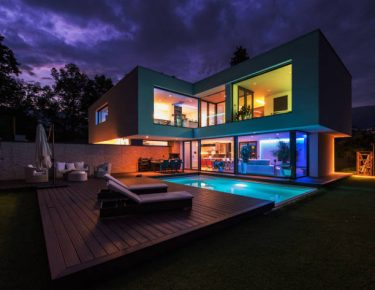 Modern villa with colored led lights at night.