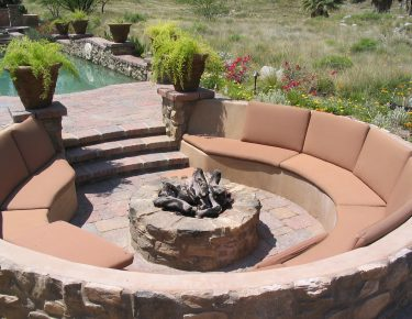 fire pit black logs surrounded with sofas and pool at side