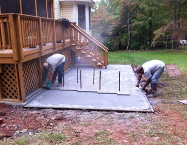 professionals stamping concrete in the backyard