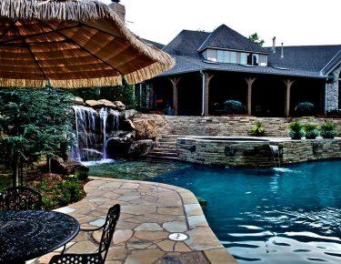 stone paved side pool patio and backyard fountain